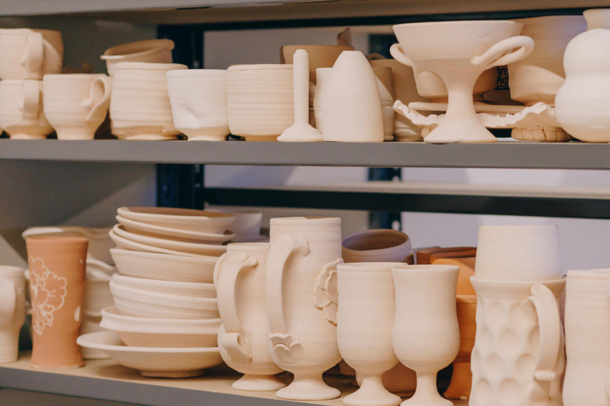 Unglazed ceramic forms sitting on a shelf