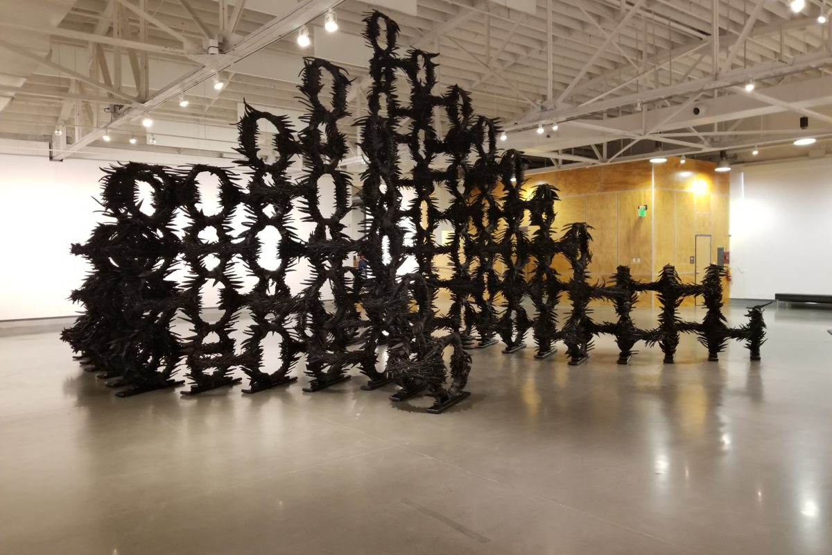 A giant sculpture of used tires and rubbers, formed into circles with spines, sits in an art gallery