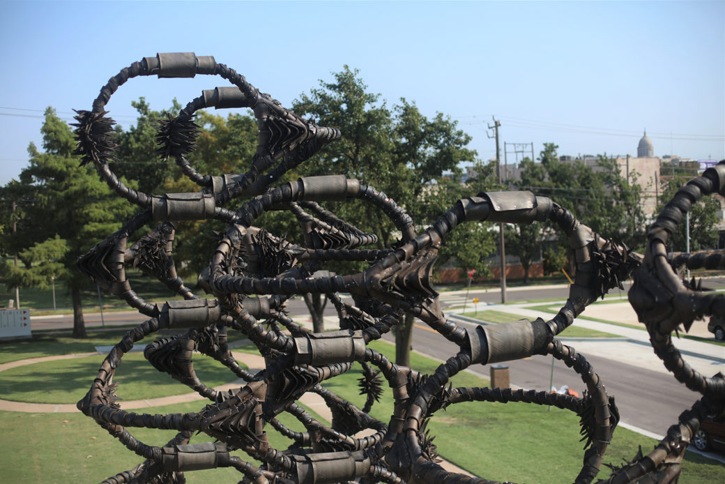 A giant sculpture -- rubber and tires twisted into towering sculptures on a metal frame -- sits in a green park