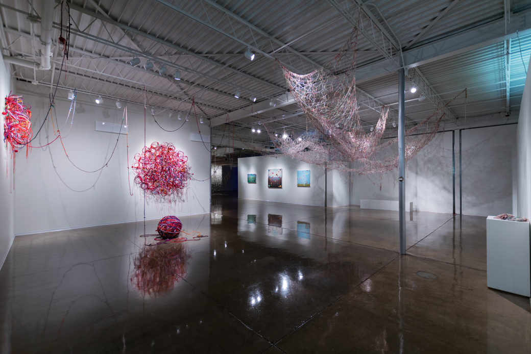 Various artworks made of red and pink string are draped around a gallery