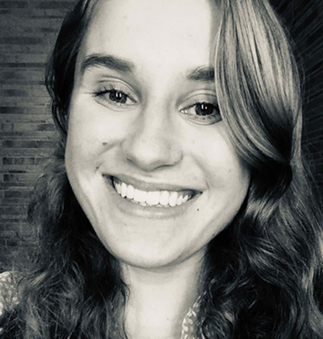 Black and white photo of a girl with long curled hair smiles at the camera.