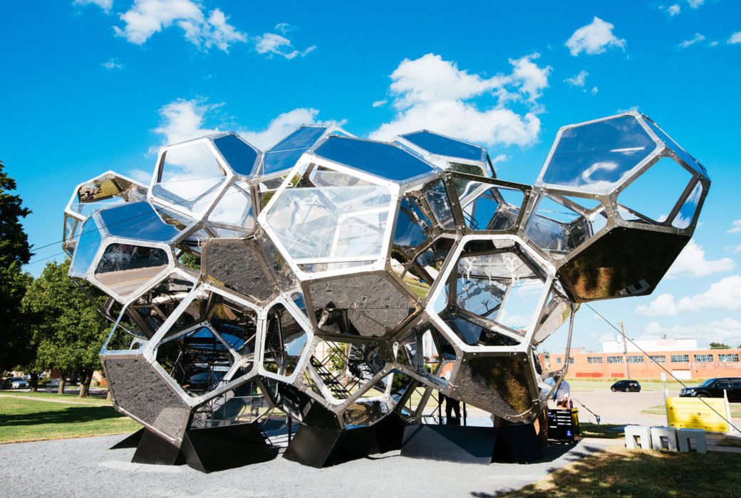 A metallic, geometric sculpture stands outdoors, reflecting the blue sky and clouds above it.