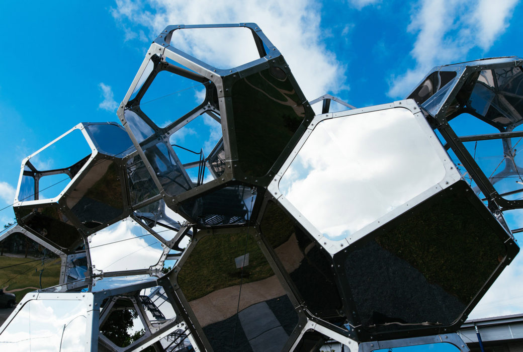 An exterior detail shot of a  large sculptur made out of metal, mirrors and see-through materials. Most of the modules that make up the sculpture are pentagons.