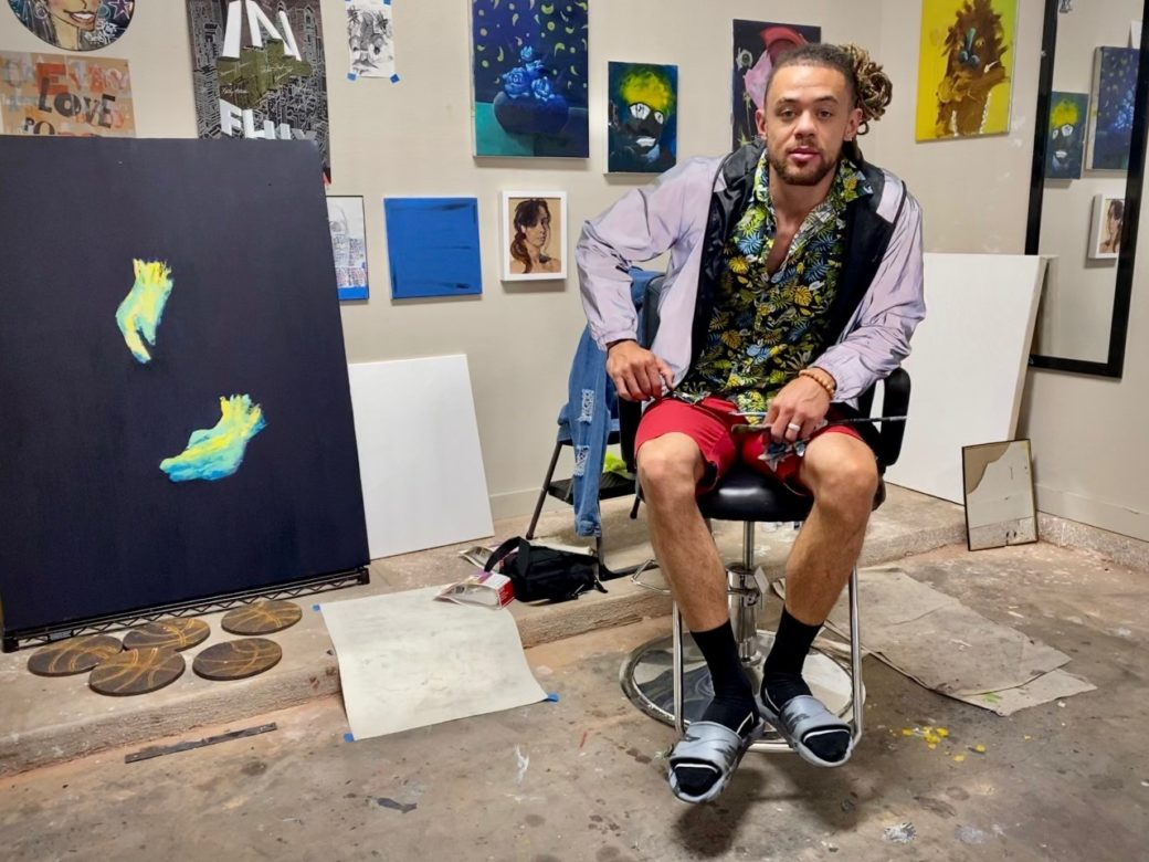 A figure in red shorts and black socks sits in a colorfully cluttered studio