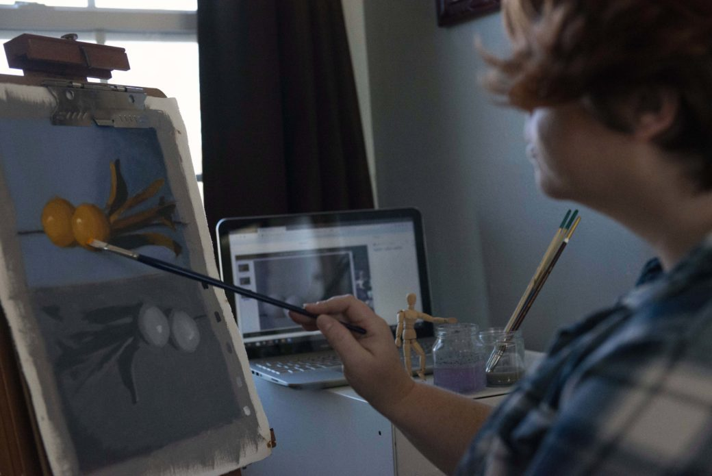 A person paints a still life in acrylic while learning from a virtual course on a laptop