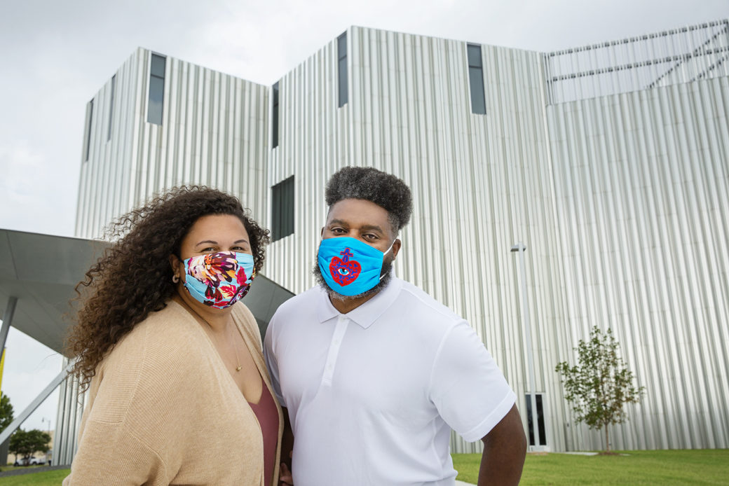 Two people wearing masks pose in front of a metallic building.