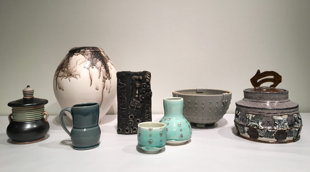 A display of eight ceramic pieces glazed in either gray, white, or blue