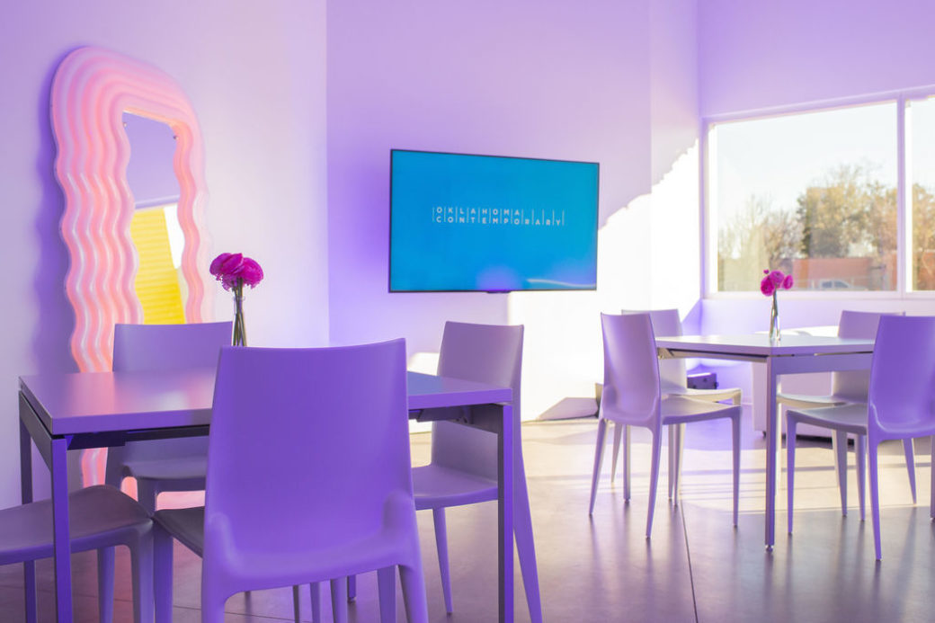 A room full of sleek, contemporary furniture, a pink art mirror and a television screen