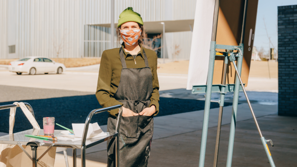 A photo of a person wearing a dark-green apron, a beanie and a mask standing outdoors next to a cart and painting easel