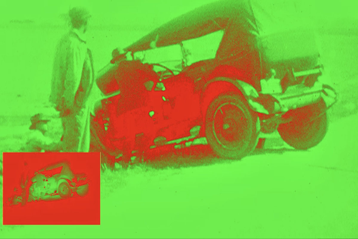 Film still -- altered to appear in lime green and bright red -- shows two figures standing near an old buggy-style car