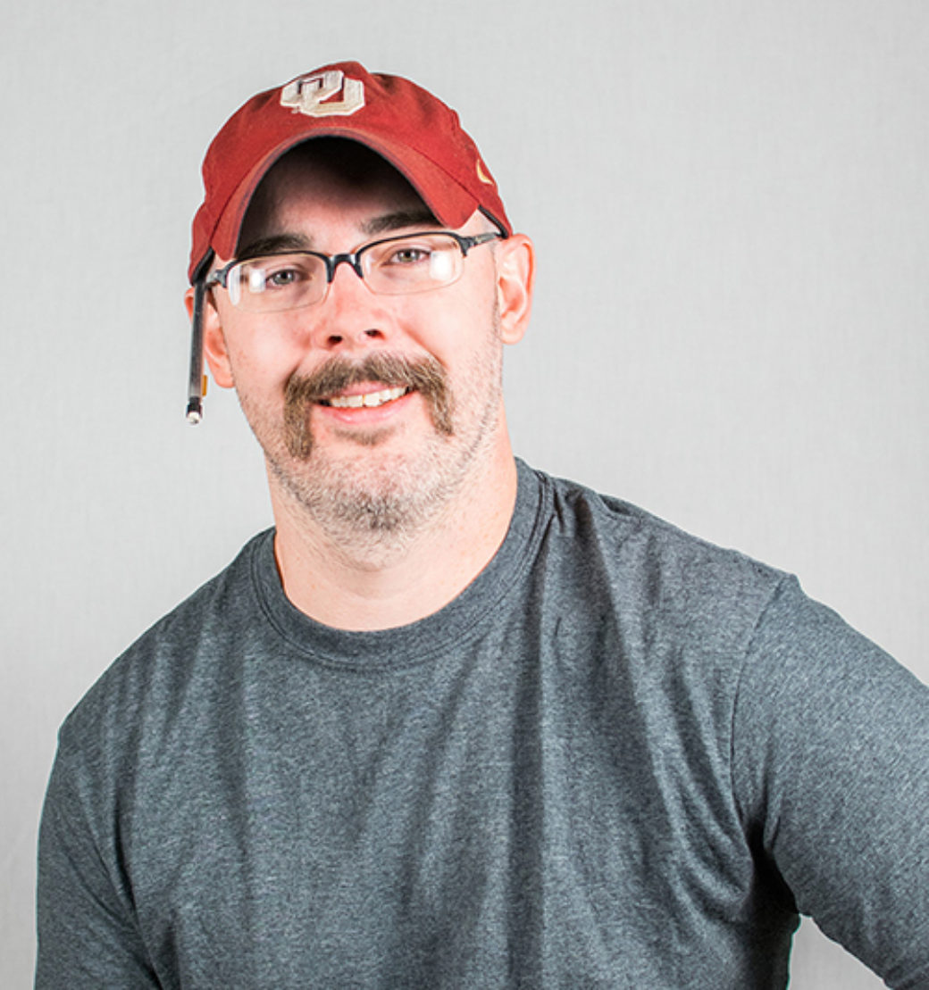 Color photo of a man with a mustache wearing a red hat smiles at the camera.