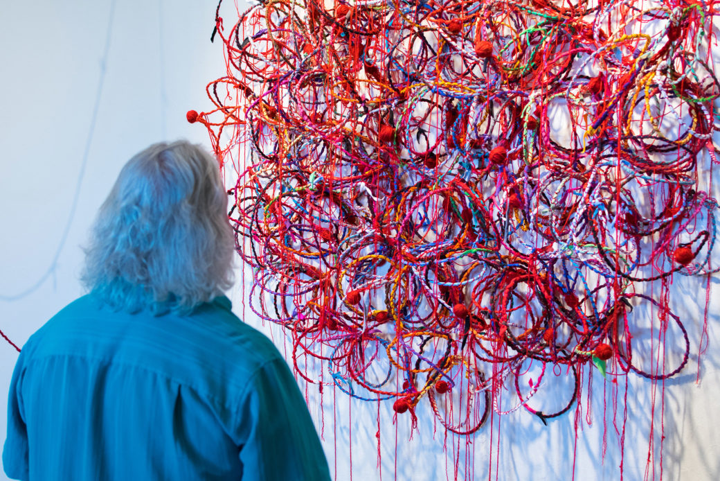 A person looks at a sculpture of red and other colored circles hanging on a wall