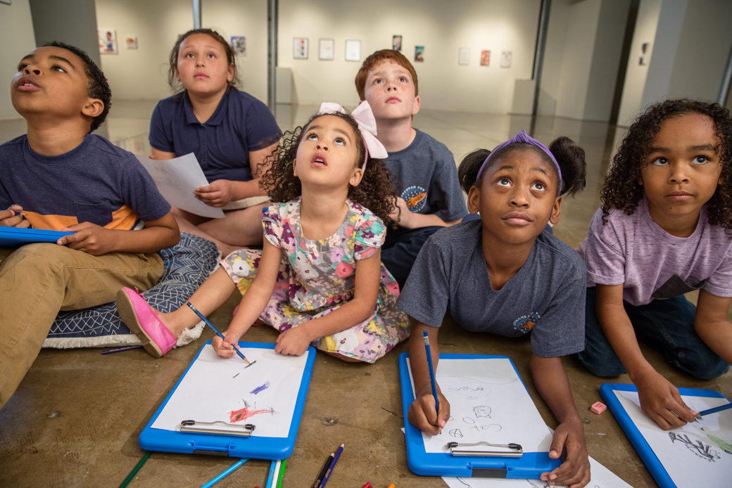 Six children sit on the floor with sketchpads and look up at something above the camera