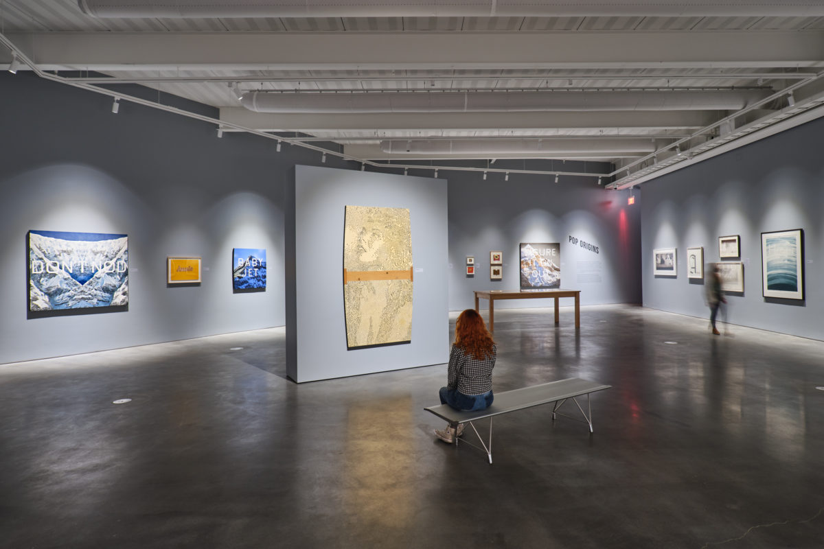 A person sits on a bench inside an art gallery with gray walls and numerous 2D works hung on the walls.