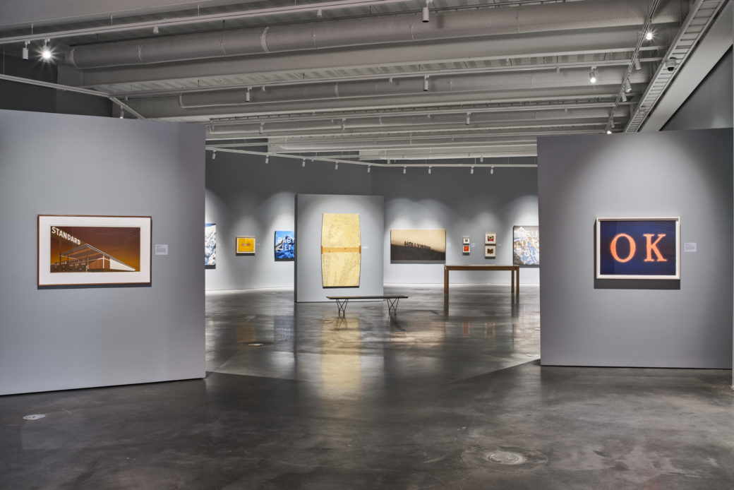 """Gallery with concrete floors and 2-D works on gray walls, including the letters """"OK"""" in orange on a blue background"""