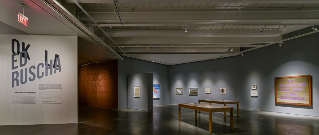 Wide view of a contemporary art gallery with work on the walls and on tables throughout the space