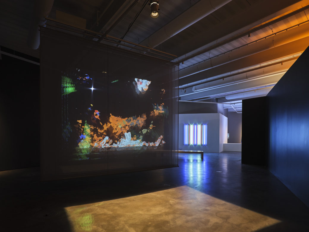 A gallery view of a contemporary art show, with an interactive light sculpture in the foreground