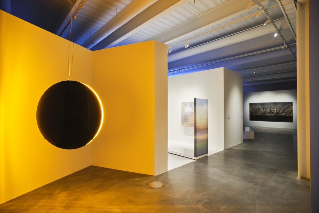 An art gallery features a black disk emitting yellow light and other installations