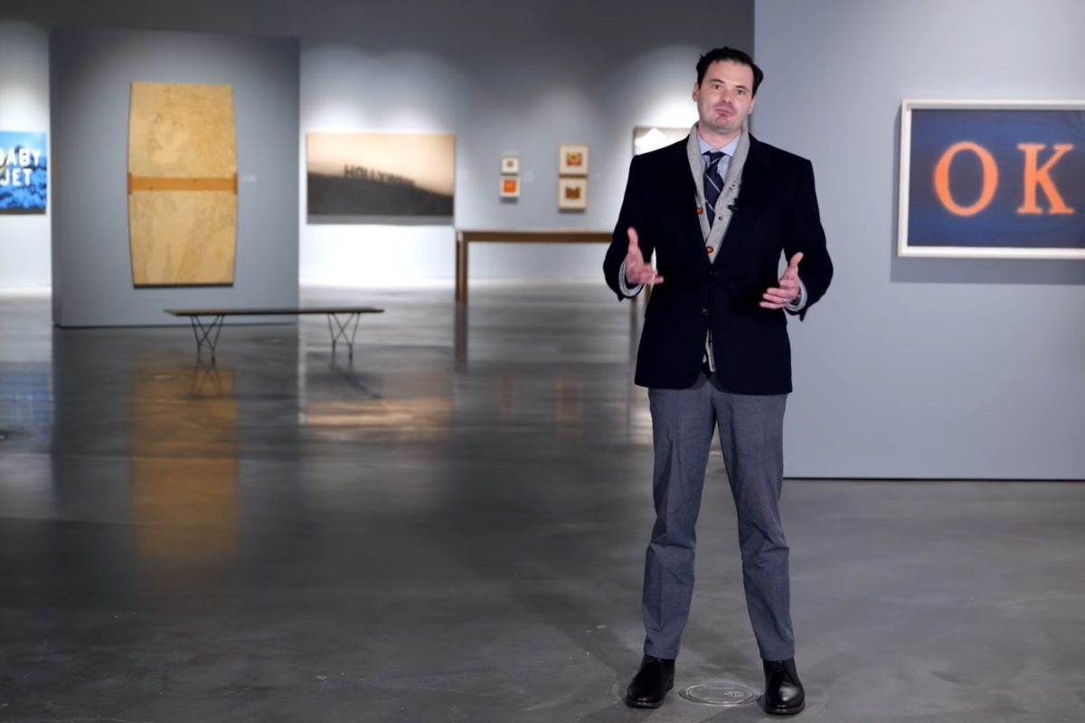 A person in a blazer and slacks stands gestures from inside an art gallery space