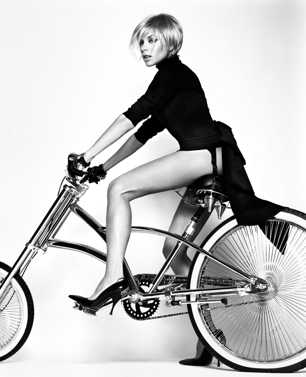 A black-and-white high fashion style photo of a figure riding a bike
