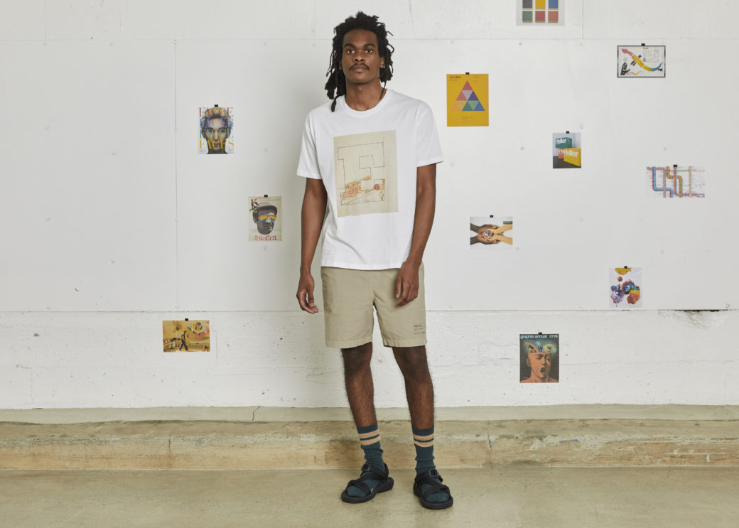 A person stands in front of a gallery wall wearing a white T-shirt emblazoned with the letter E