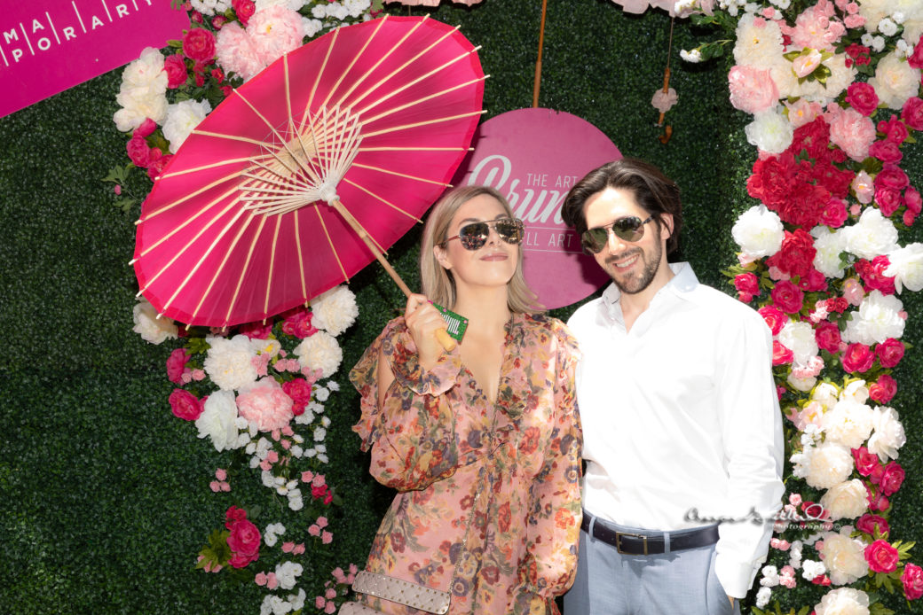 A couple in sunglasses poses with a parasol in front of a wall of greenery and flowers