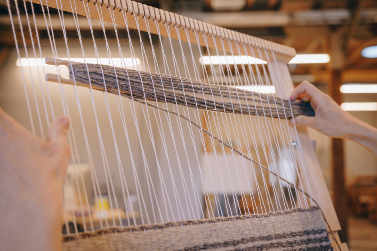 Hands weaving on a loom
