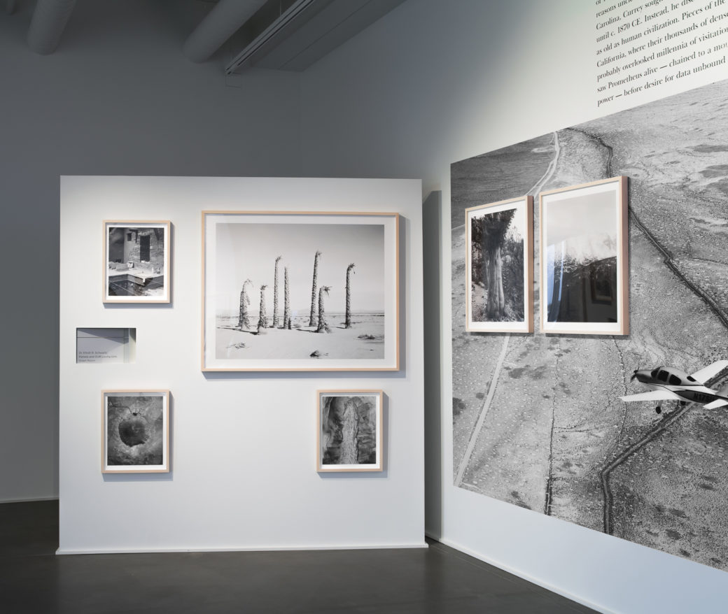 A photo of a corner in an art gallery featuring a block of text and a large black-and-white photo in vinyl plus framed photos