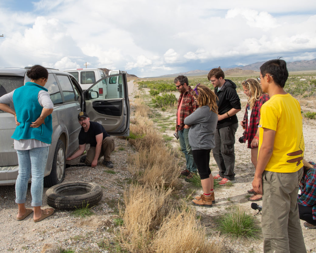 A group of people watch as one person changes the tire on a minivan in a desert setting