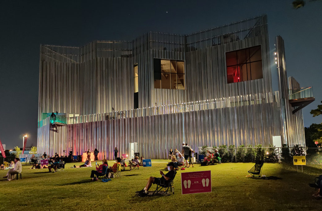 People sit in camp chairs on a green lawn at night with a silver building in the background