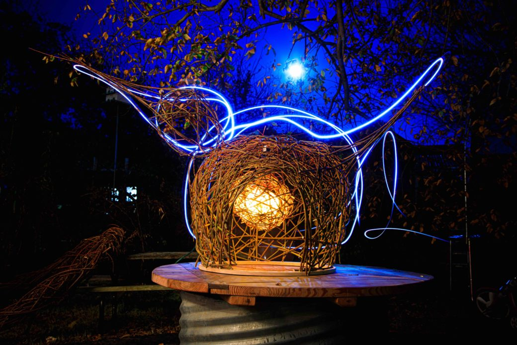 A spherical sculpture of brown, nest-like materials with blue lights interwoven in the outline