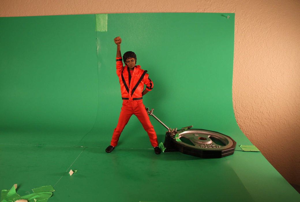 A dark-skinned doll in a red tracksuit stands on a green background next to mechanical, gear-like item