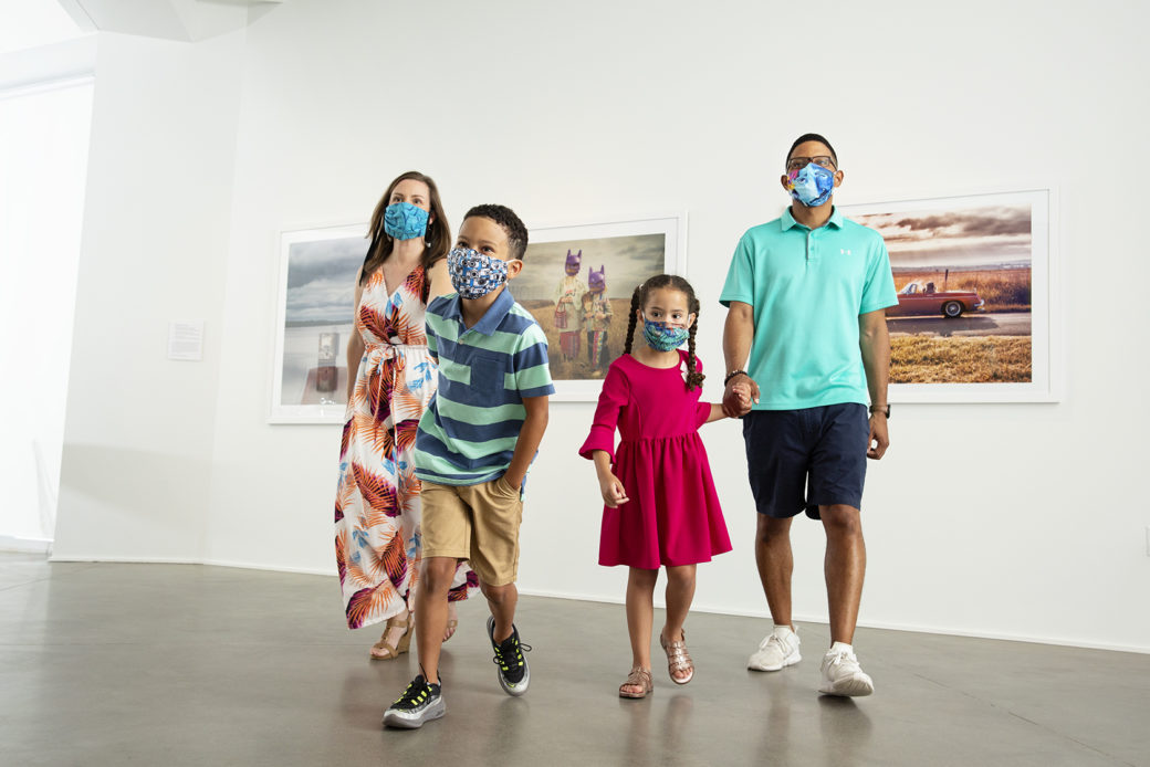 A young family (two parents and two children, in masks) walk through an art gallery