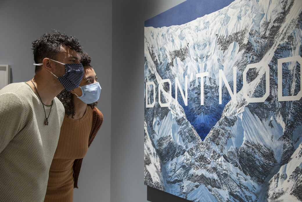 "A couple wearing masks looks at a large painting of mountains overlaid with the words ""DON'T NOD"""