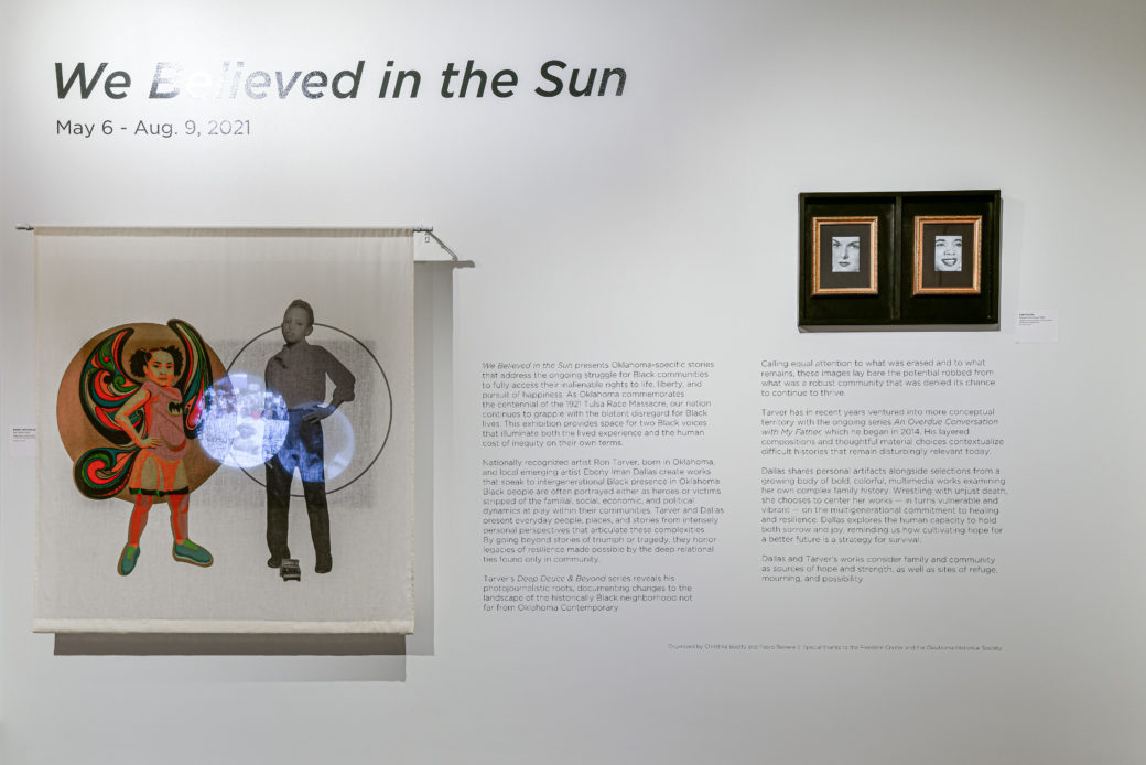 """A gallery wall features the words """"We Believed in the Sun,"""" a block of text and a screen with images on it over a monitor"""