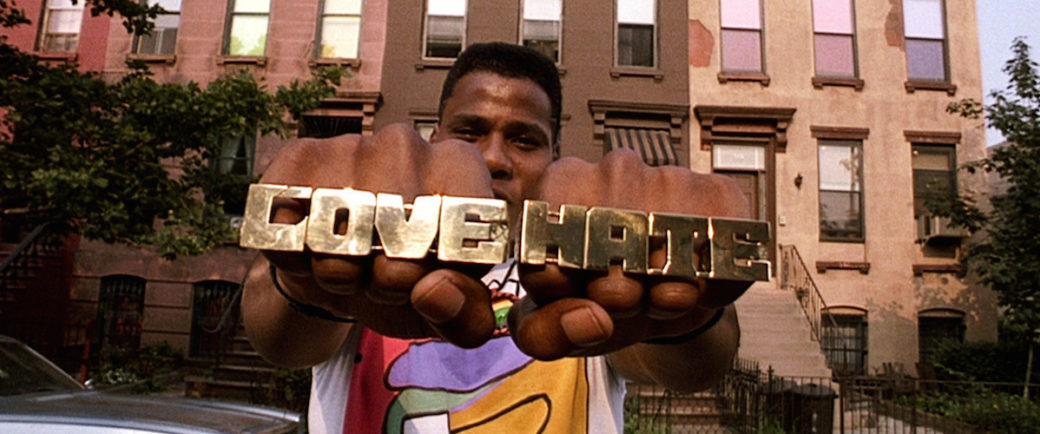 """A Black person with short hair displays gold jewelry across their knuckles, featuring the words """"LOVE"""" and """"HATE"""""""
