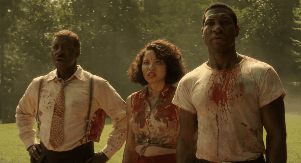 Three Black people stand in a field with their clothes covered in blood, muck and dirt