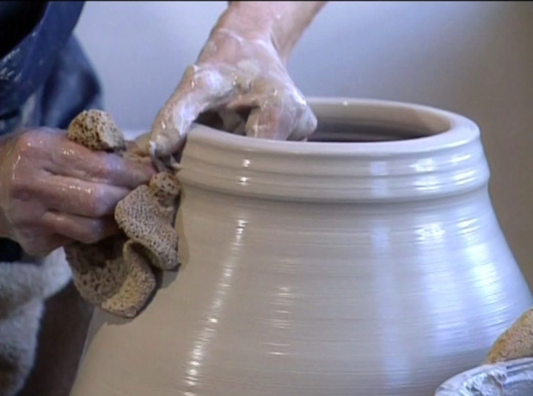 Hands shape a clay pot on a ceramics wheel