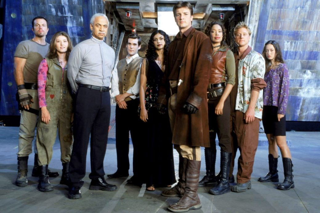 A group of people stand in front of the opening to a spaceship