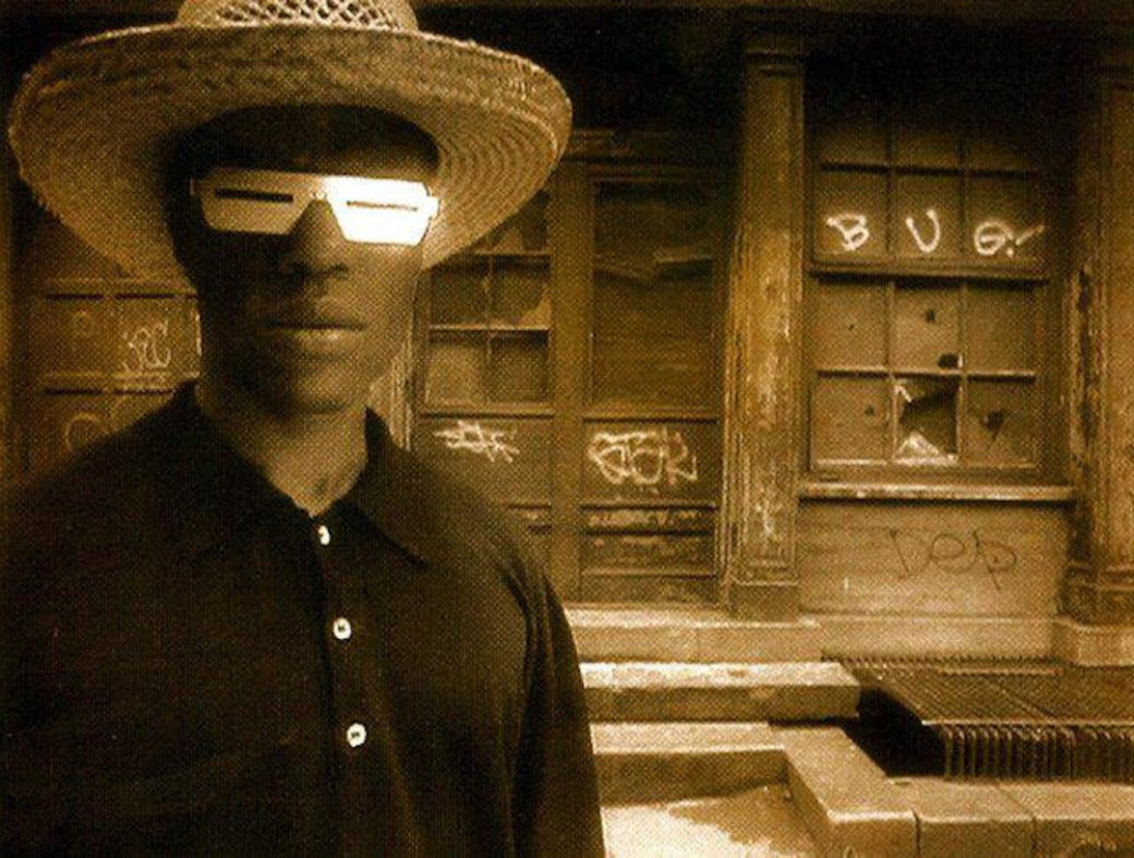 A figure in a wide-brimmed hat and futuristic sci-fi glasses looks into the camera in a sepia-toned photograph