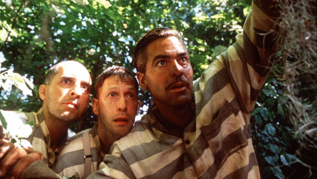 Three figures in turn-of-the-century prison fatigues gaze off camera