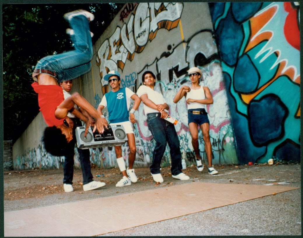 A young breakdancer does a backflip before a crowd dressed in early 1980s garb