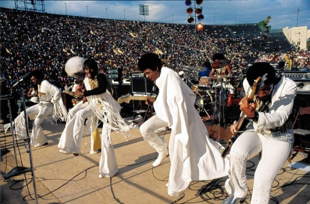 A funk band performs in white suits in a crowded stadium