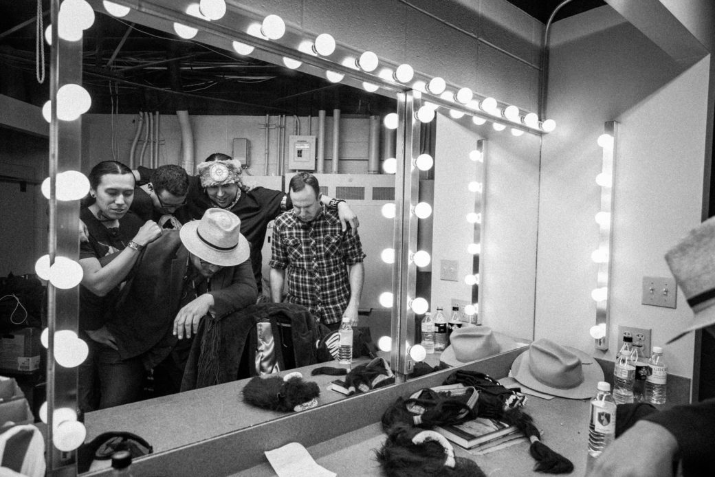 Five people huddle together in front of a lit mirror backstage