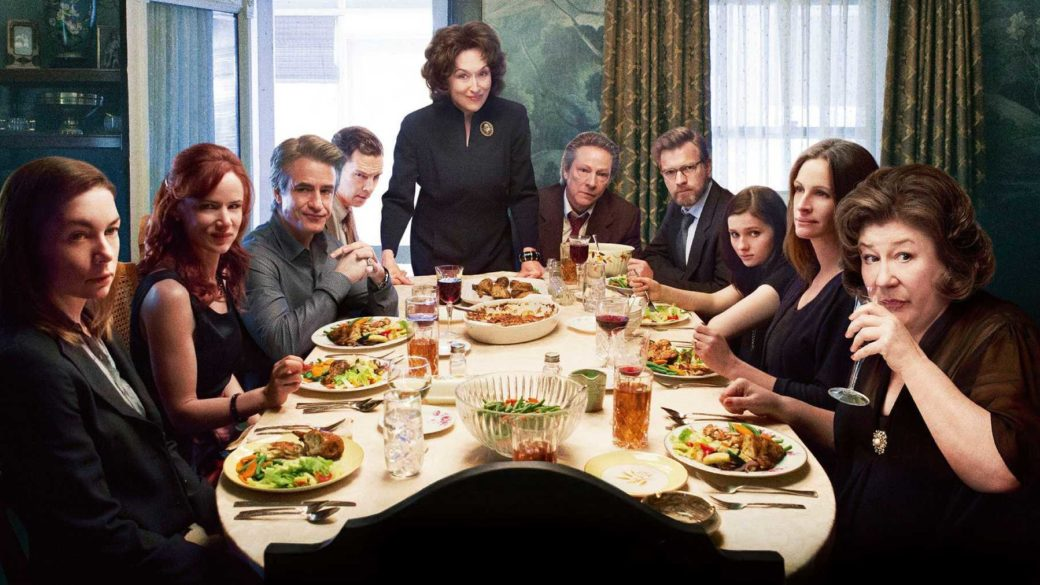 A still from the film August: Osage County depicts a large family sitting around a table and looking into the camera