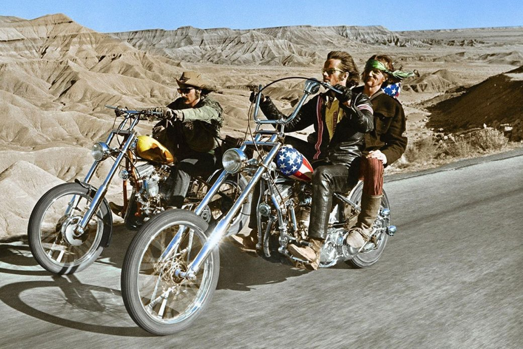 Three people ride through the desert of the American West on two motorcycles