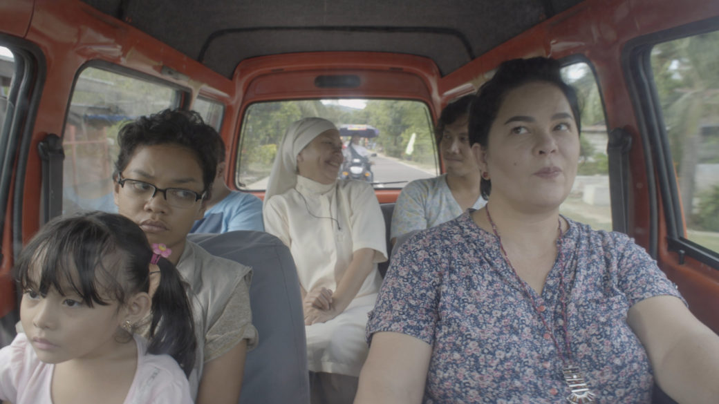 A family of six is packed into a small car on a road trip