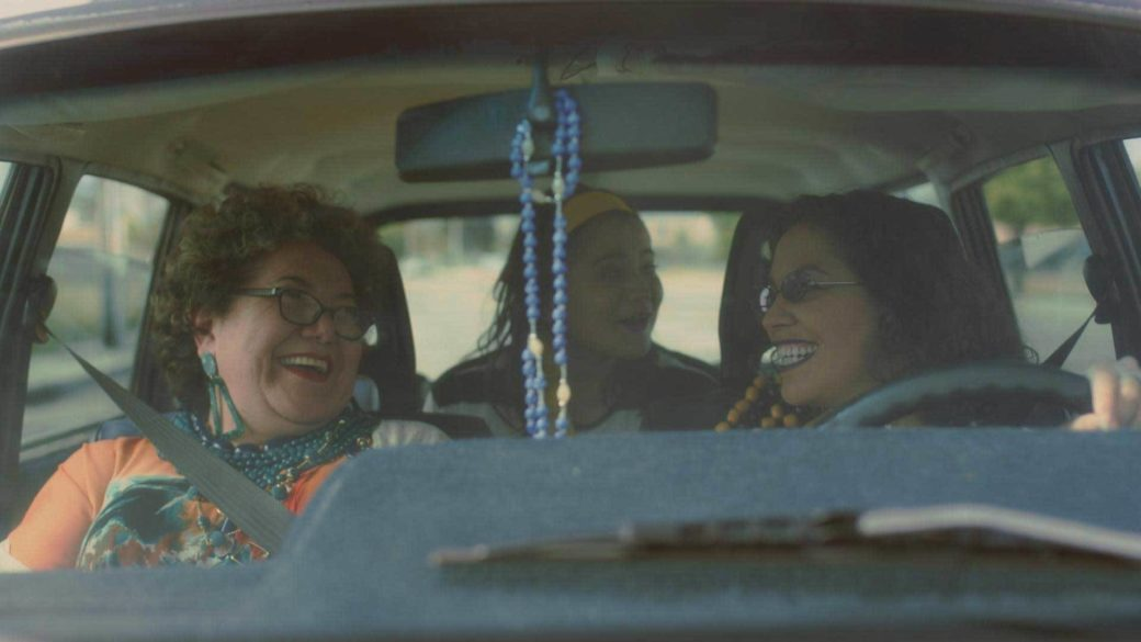 A car full of people laughing, with prayer beads wrapped around the mirror