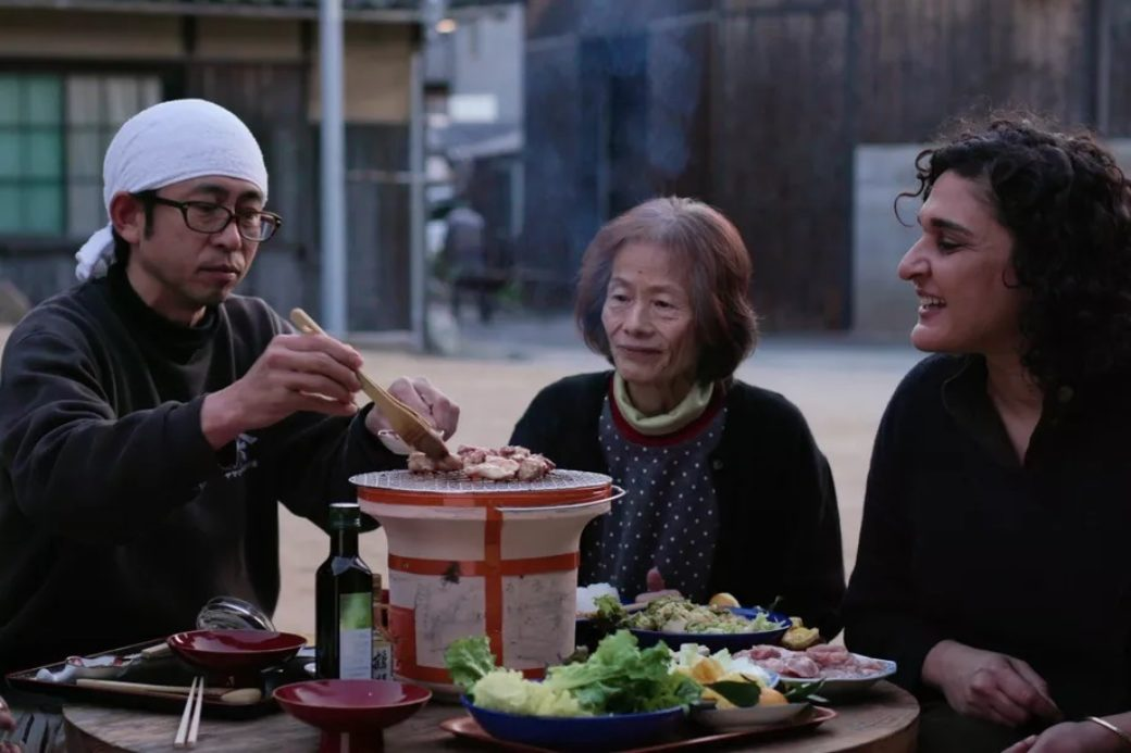 Three figures share a tabletop Korean barbecue outdoors