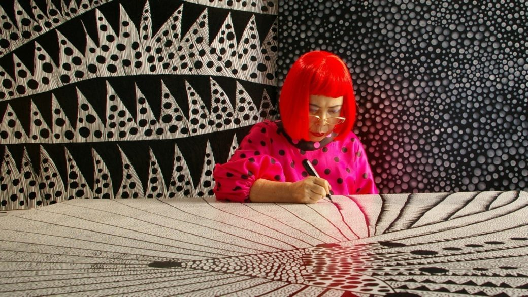 An elderly woman in bright clothes draws on a large white surface with a black marker, as behind her black and white pattern walls